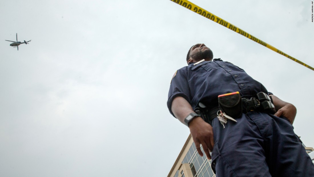 A helicopter hovers overhead as a police officer stands guard on July 2.