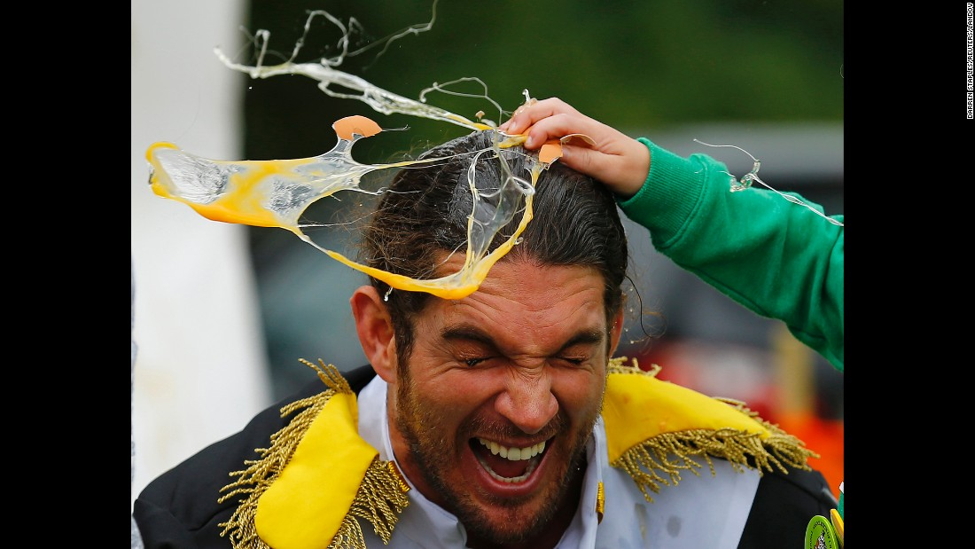 A man has an egg smashed on his head to raise money for charity Sunday, June 28, at the World Egg Throwing Championships in Swaton, England.