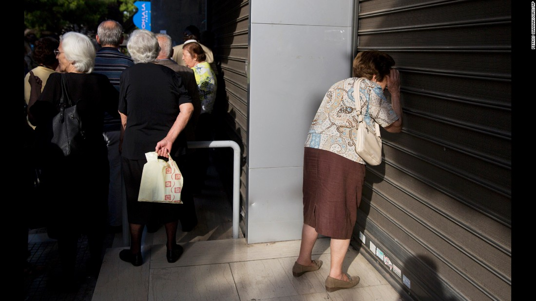 "A woman in Athens, Greece, looks through the closed shutters of a bank on Monday, June 29. Greek banks <a href=""http://money.cnn.com/2015/06/28/news/economy/greece-banks-ecb/"" target=""_blank"">stayed shut on Monday</a> as officials scrambled to prevent the country's financial system from collapsing in panic."