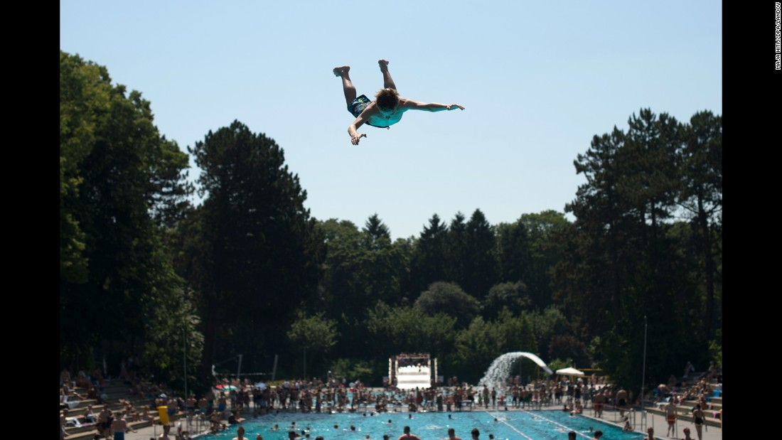 A young person jumps into a swimming pool in Cologne, Germany, on Thursday, July 2.