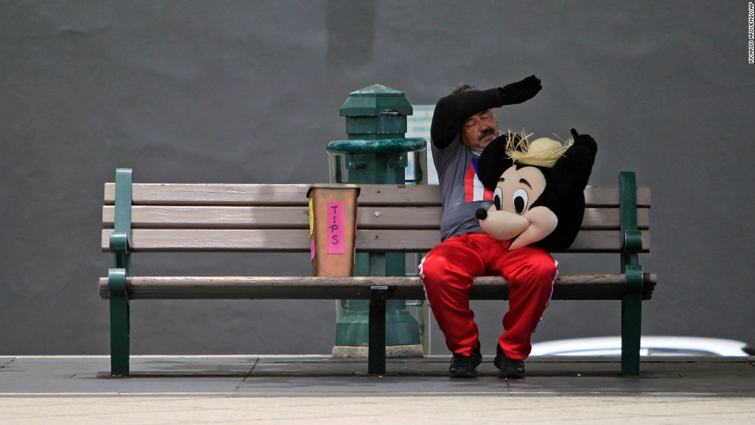 A street performer in a Mickey Mouse costume rests on a bench in San Juan, Puerto Rico, on Wednesday, July 1.