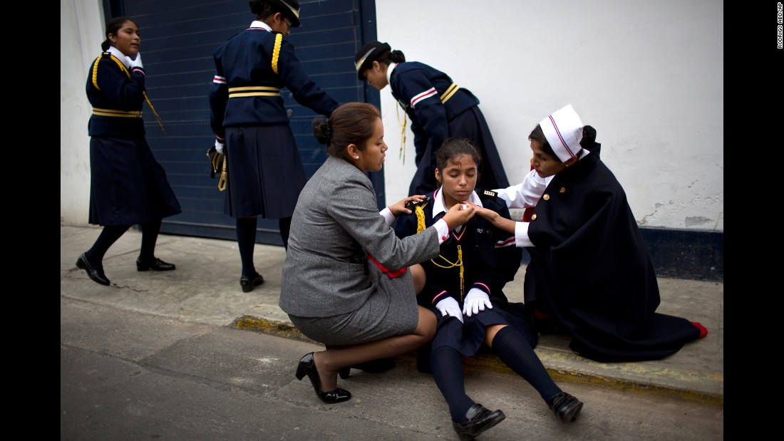 A student in Lima, Peru, is assisted by teachers after she fell ill while marching in a parade celebrating St. Peter's Day on Monday, June 29.