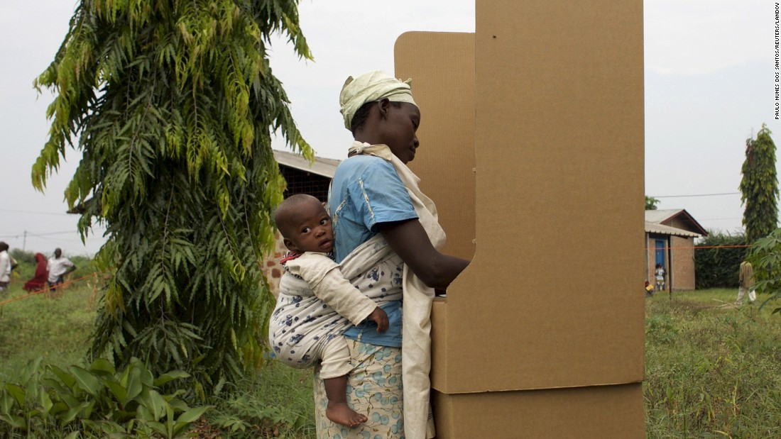 A woman carrying a child casts her vote in Burundi's parliamentary election on Monday, June 29.