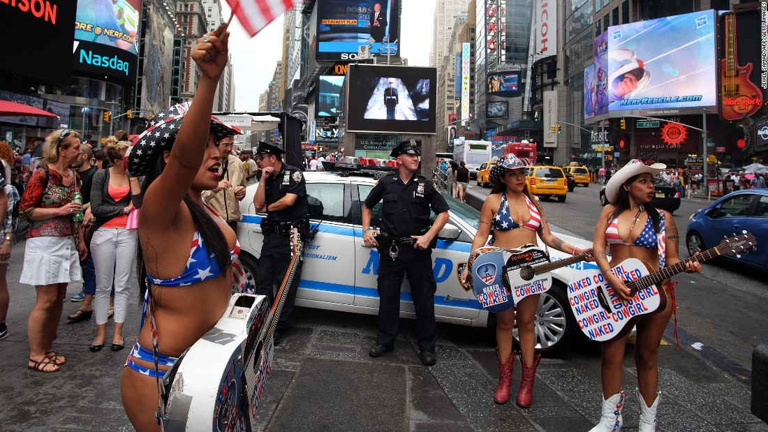 Show girls cheer as NYPD officers keep vigil in Times Square on Saturday.