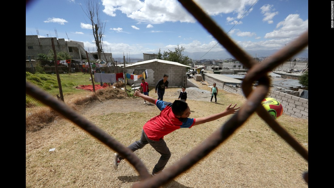Steven Ordonez, 13, in the center back, hits the soccer ball past a goalie in a makeshift soccer game at his neighbor's house in North Quito.