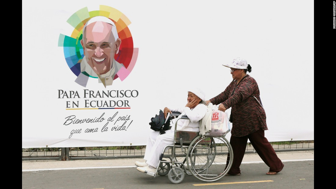 A woman is wheeled past a banner with an image of Pope Francis at Samanes Park on July 5.