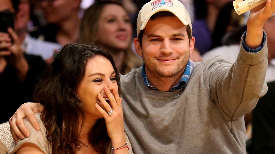 "LOS ANGELES, CA - DECEMBER 19:  Actors Ashton Kucher and Mila Kunis react after being shown on the video board during the ""kiss me camera"" feature during the game between the Oklahoma City Thunder and the Los Angeles Lakers at Staples Center on December 19, 2014 in Los Angeles, California.  NOTE TO USER: User expressly acknowledges and agrees that, by downloading and or using this photograph, User is consenting to the terms and conditions of the Getty Images License Agreement.  (Photo by Stephen Dunn/Getty Images)"