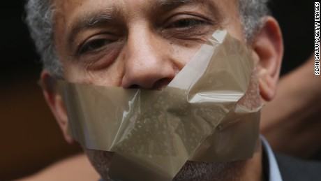 A protester demanding freedom for Al Jazeera reporter Ahmed Mansour stands with his mouth taped shut to symbolize the persecution of journalists in Egypt outside the court and prison where Mansour is being held on June 22, 2015 in Berlin, Germany.