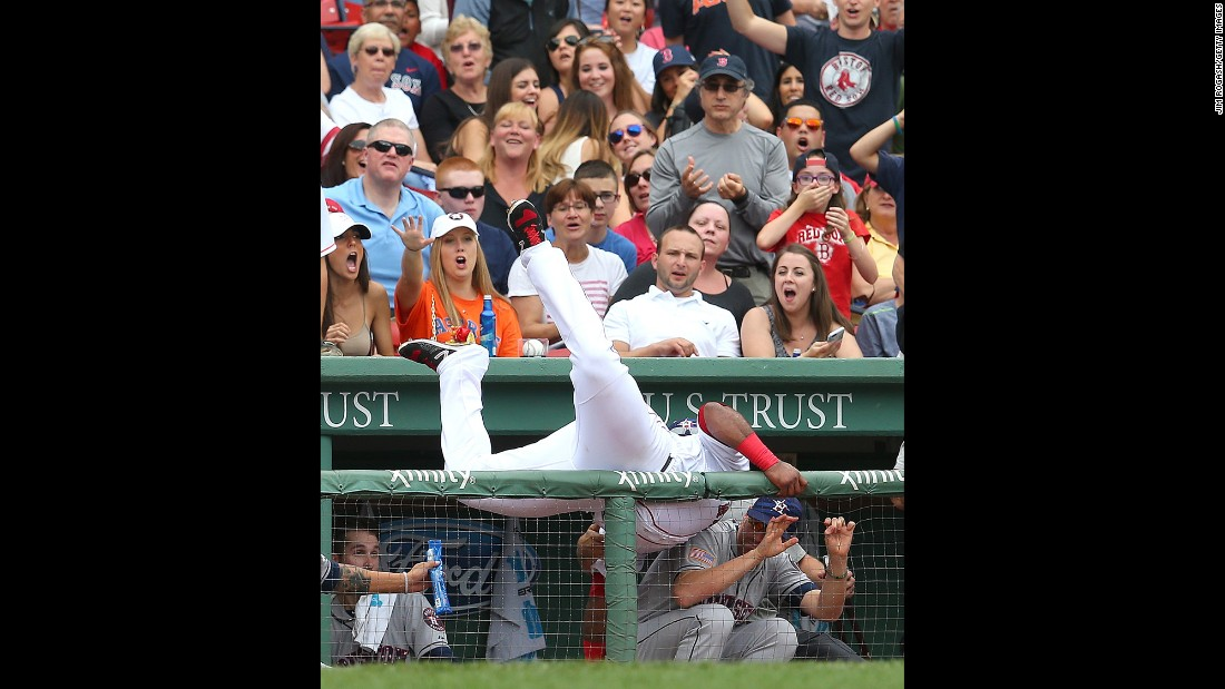 Boston's Pablo Sandoval falls into Houston's dugout while catching a ball Saturday, July 4, in Boston's Fenway Park.