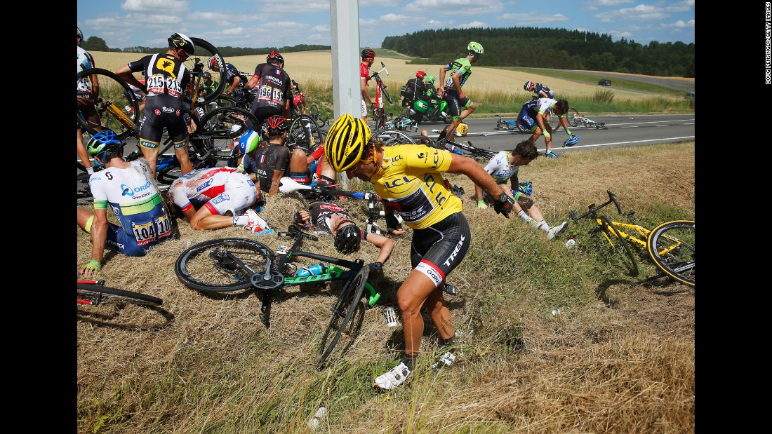 "Cyclists recover on the ground after <a href=""http://bleacherreport.com/articles/2515851-huge-crash-takes-out-riders-on-stage-3-of-the-tour-de-france?utm_source=cnn.com&utm_medium=referral&utm_campaign=editorial"" target=""_blank"">a massive crash</a> in the third stage of the Tour de France on Monday, July 6. The man in the foreground, Swiss cyclist Fabian Cancellara, was leading the race, but he had to withdraw after suffering two fractured vertebrae."