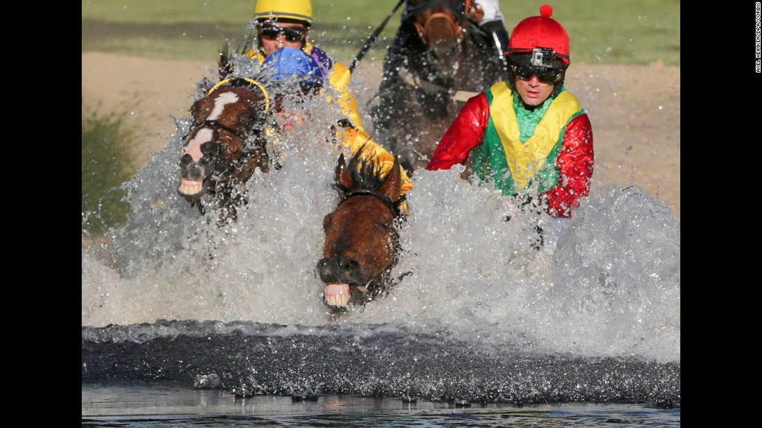 Horses race through a water obstacle during an equestrian event in Hamburg, Germany, on Tuesday, June 30.