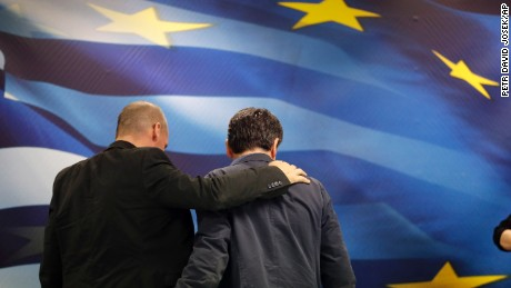New Greek Finance Minister Euclid Tsakalotos, right, and outgoing Finance Minister Yanis Varoufakis leave together after a hand over ceremony in Athens, Monday, July 6, 2015. Despite triumphing in a popular referendum vote against austerity, Greece on Monday faced the urgent need to heal its ties with European creditors and reach a financial rescue deal that might prevent it from falling out of the euro,  (AP Photo/Petr David Josek)