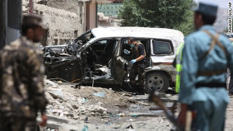 Security personnel inspect a damaged vehicle after a suicide attack that targeted a NATO convoy in Kabul.