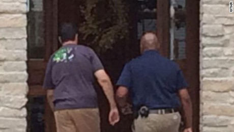 Ex-Subway pitchman Jared Fogle, left, walks back into his Zionsville, Indiana, home as investigators search it.