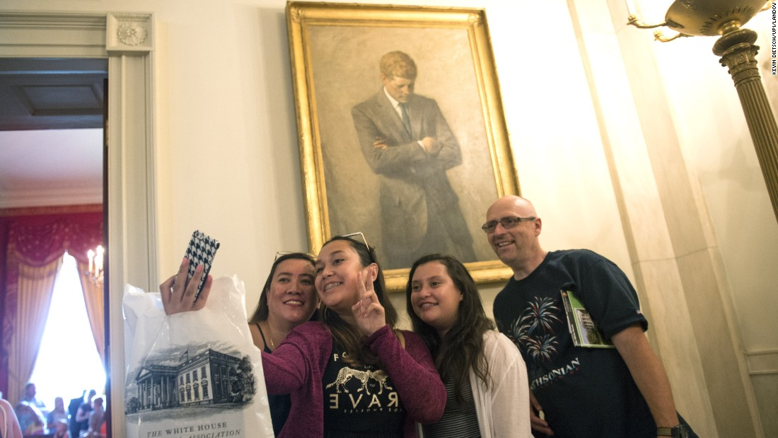 During a tour of the White House, a family takes a selfie in front of a portrait of former U.S. President John F. Kennedy on Wednesday, July 1. The White House now allows photos to be taken during public tours.