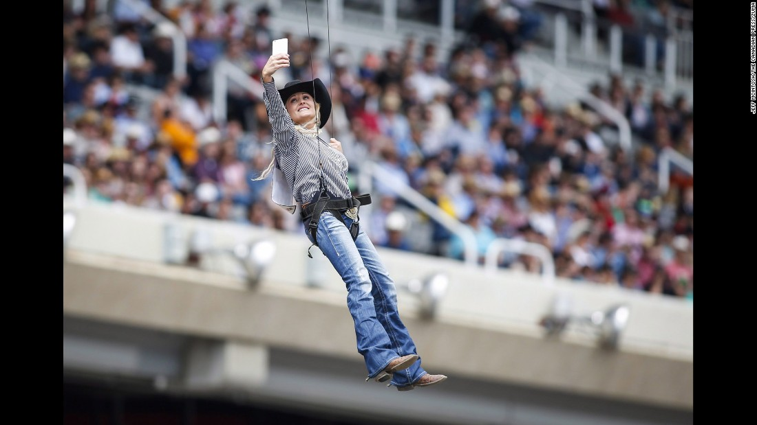 Barrel racer Carlee Pierce snaps a selfie Sunday, July 5, as she is lowered to the ground during opening ceremonies for the Calgary Stampede in Calgary, Alberta.