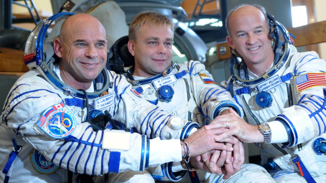 Canadian space tourist and founder of Cirque du Soleil Guy Laliberte (L), Russian cosmonaut Maxim Surayev (C) and US astronaut Jeff Williams (R) shake hands during a training session outside Moscow in Star City on September 9, 2009. The crew is set to travel from the Baikonur cosmodrome in a Russian Soyuz TMA-16 rocket to the international space station in late September. AFP PHOTO / DMITRY KOSTYUKOV (Photo credit should read DMITRY KOSTYUKOV/AFP/Getty Images)