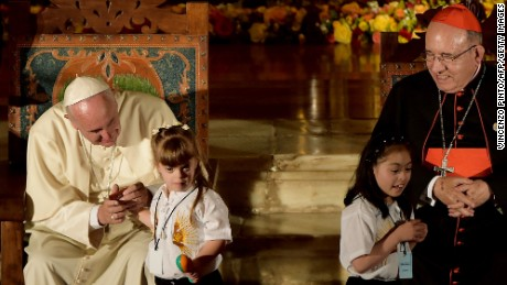 Pope Francis (L) holds a little girl's hand during a meeting with political, economic and civil leaders at San Francisco Church in Quito, Ecuador, on July 7.