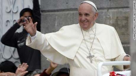 Pope Francis waves as he rides in the Popemobile through the Ecuadorean capital, Quito, on July 7, 2015.