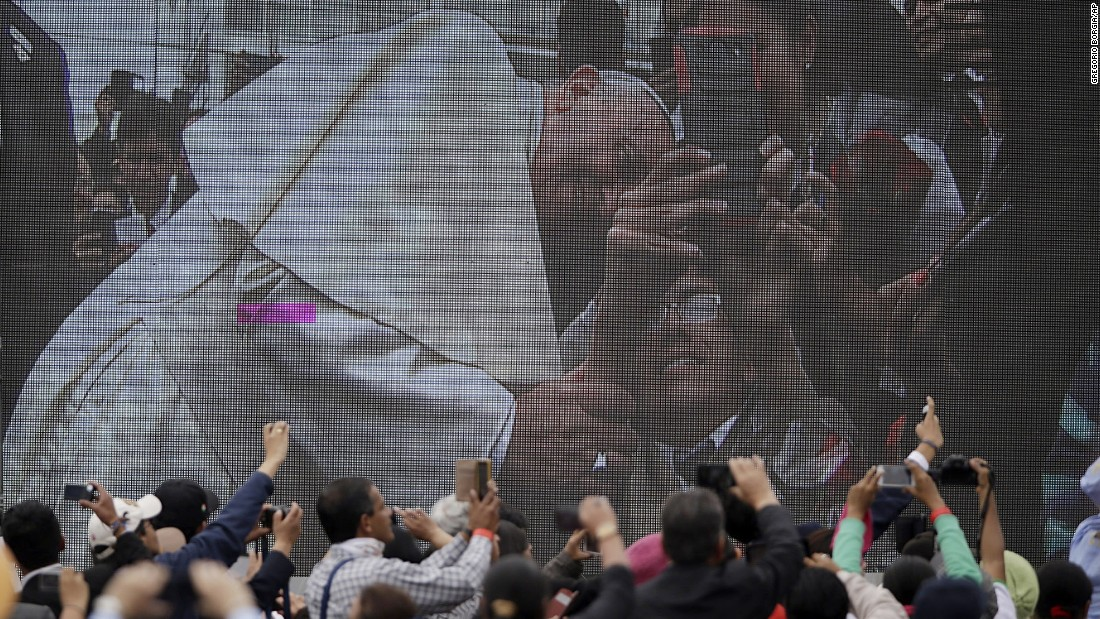 A crowd watches Francis on a video screen as he poses for a selfie during his visit to the Catholic University in Quito on July 7.