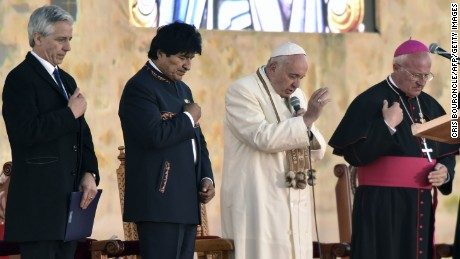 Pope Francis (2nd L) speaks next to Bolivian President Evo Morales and vice president Alvaro Garcia Linera (L) upon arrival to El Alto, a plateau over La Paz, 4,000 meters above sea-level, on his first visit to Bolivia on July 8, 2015. Pope Francis, the first Latin American pontiff, arrived in Bolivia on the second leg of a three-nation tour of the continent's poorest countries, where he has been acclaimed by huge crowds.   AFP PHOTO / CRIS BOURONCLE        (Photo credit should read CRIS BOURONCLE/AFP/Getty Images)