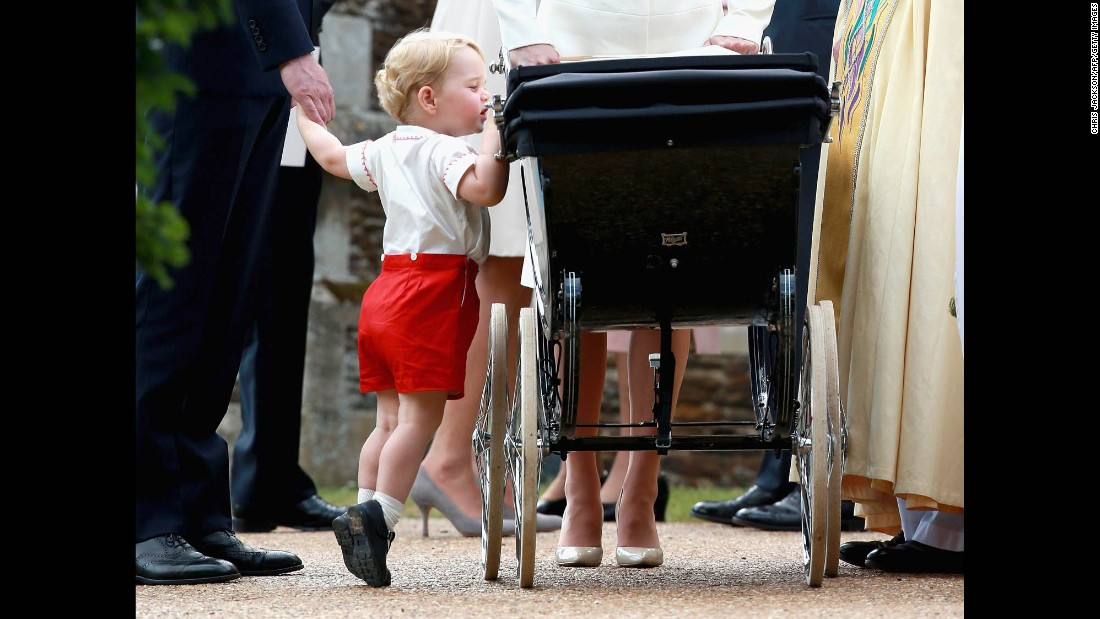 Prince George looks at his sister after the christening.