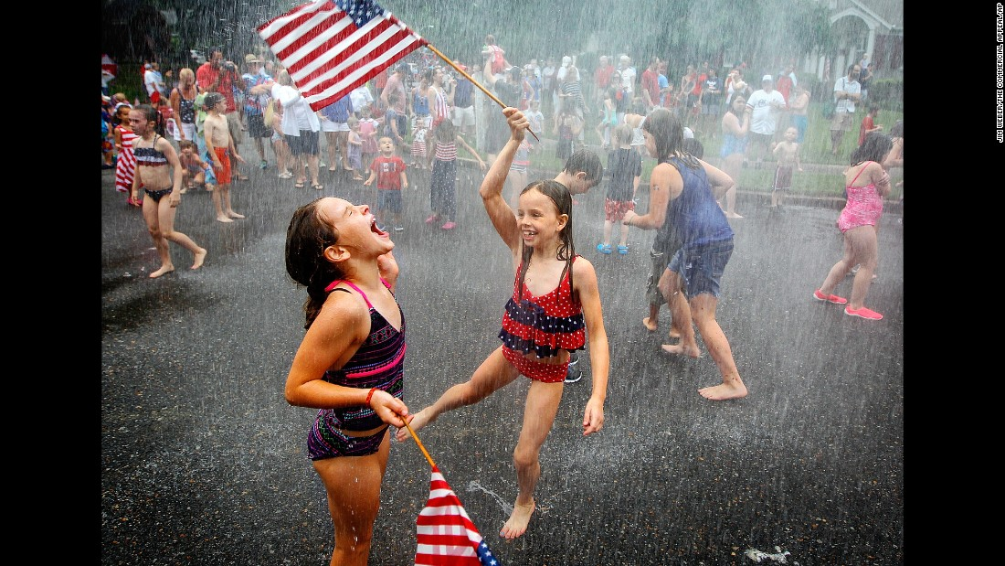 Children play under the spray of a fire hose after a Fourth of July parade in Memphis, Tennessee.