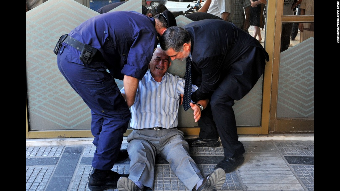 "A crying man is assisted by a bank employee and a police officer outside a national bank branch in Thessaloniki, Greece, on Friday, July 3. Pensioners in the cash-strapped country <a href=""http://money.cnn.com/2015/07/03/news/economy/greece-crisis-depression/"" target=""_blank"">were limited to taking just 120 euros out of their accounts.</a>"