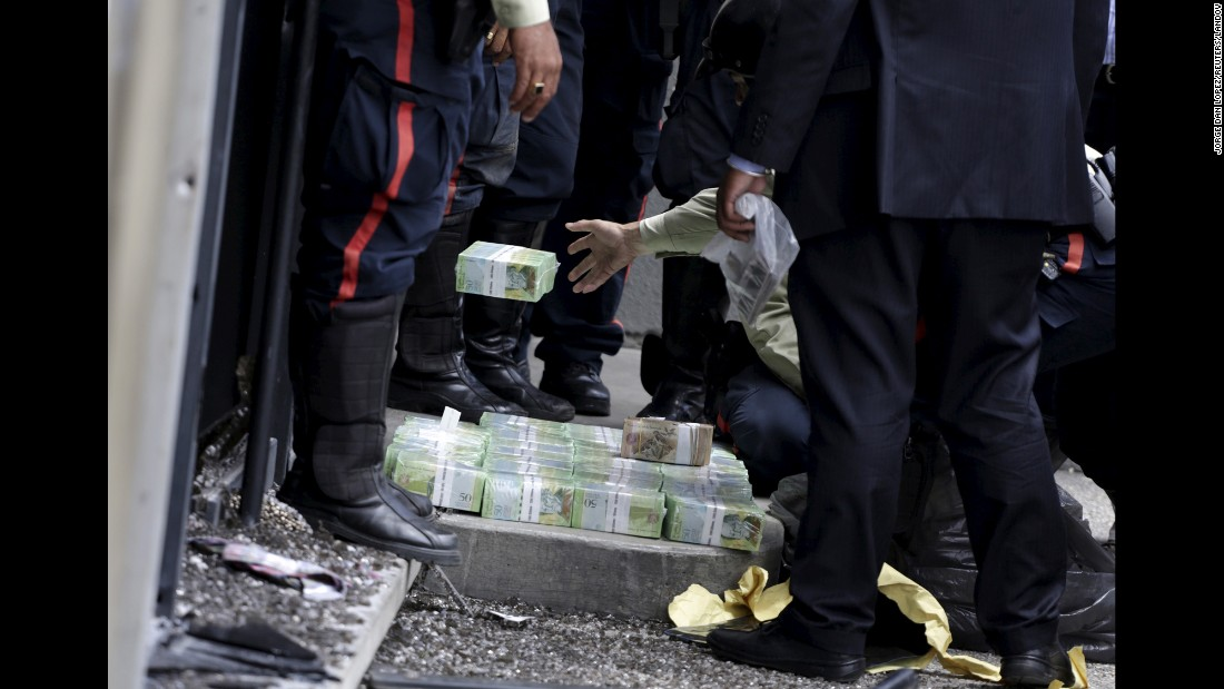 A police officer throws banknotes after a bank robbery was thwarted in Caracas, Venezuela, on Monday, July 6.