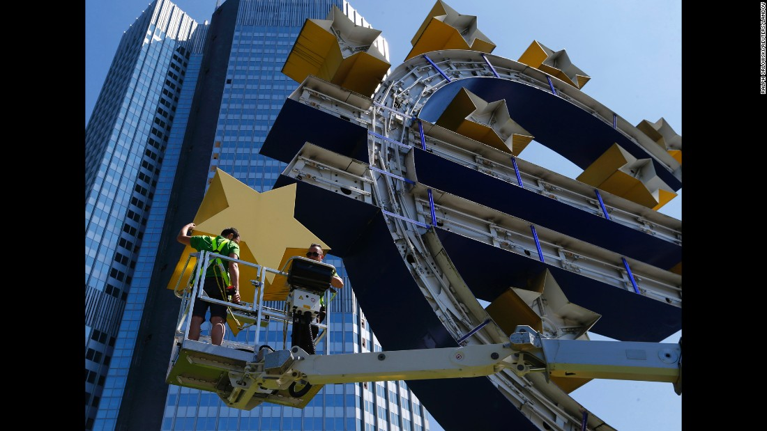 Workers in Frankfurt, Germany, dismantle a euro sign sculpture for maintenance Monday, July 6, in front of the former headquarters of the European Central Bank.