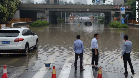 Citizens stand by a heavily flooded area after after a strong downpour hit Shanghai on June 17, 2015. The National Meteorological Centre of China has issued a yellow alert for heavy rain in south and east China, state media reported. CHINA OUT AFP PHOTOSTR/AFP/Getty Images