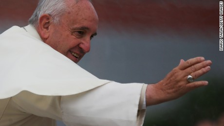 Caption:SANTA CRUZ, BOLIVIA - JULY 09: Pope Francis waves to the crowd from the Popemobile while making his way to celebrate an open-air Mass on July 9, 2015 in Santa Cruz, Bolivia. Pope Francis will visit a notorious Bolivian prison in Santa Cruz July 10 during his three-country swing through Ecuador, Bolivia and Paraguay. (Photo by Mario Tama/Getty Images)