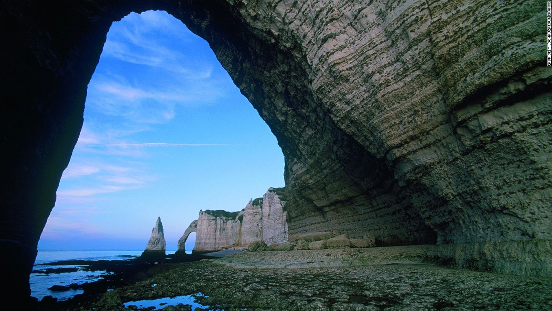 Soaring natural arches formed by coastal erosion are the key attraction at Etretat, a small town on Normandy's Alabaster Coast.