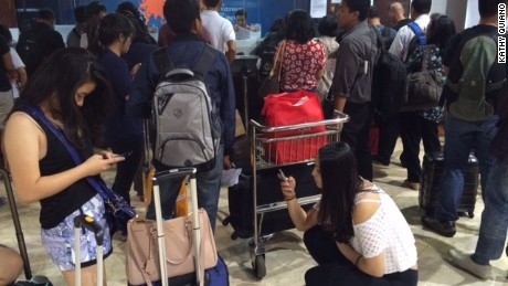 Stranded travelers wait at Jakarta International Airport on July 10 after volcanic ash in Indonesia caused flight cancellations and airport closures.