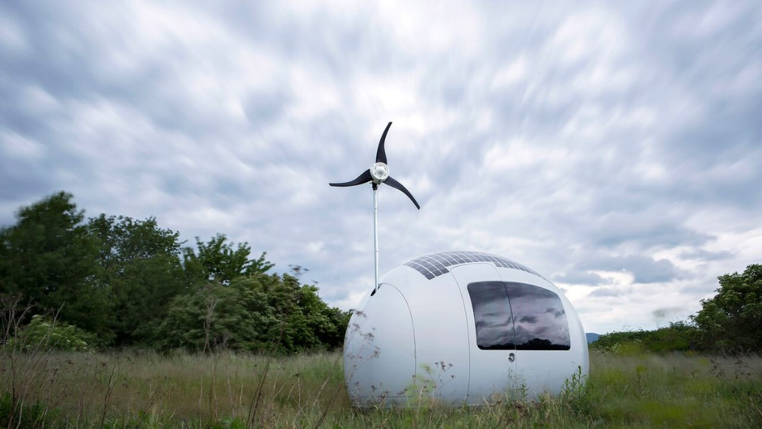The capsule harvests energy through a layer of solar cells and a retractable wind turbine.