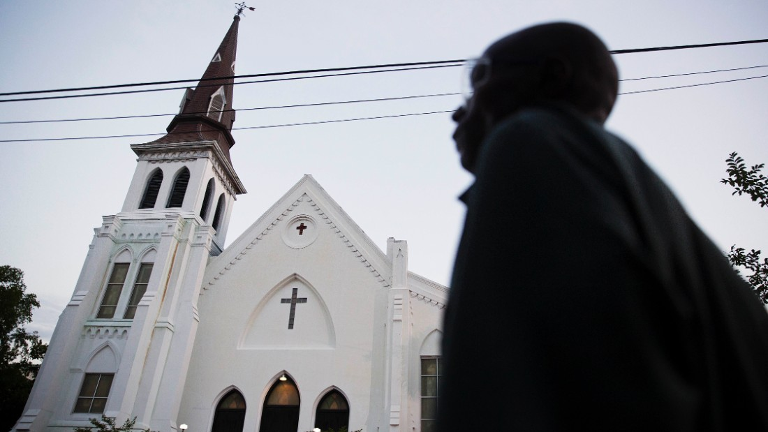 The steeple of Emanuel African Methodist Episcopal Church stands as a pedestrian passes early Sunday, June 21, 2015, in Charleston, S.C. Members of a historic black church in the U.S. will return to their sanctuary Sunday and worship less than a week after a white gunman killed nine people there, and similar sermons of recovery and healing will reverberate throughout the country. (AP Photo/David Goldman)