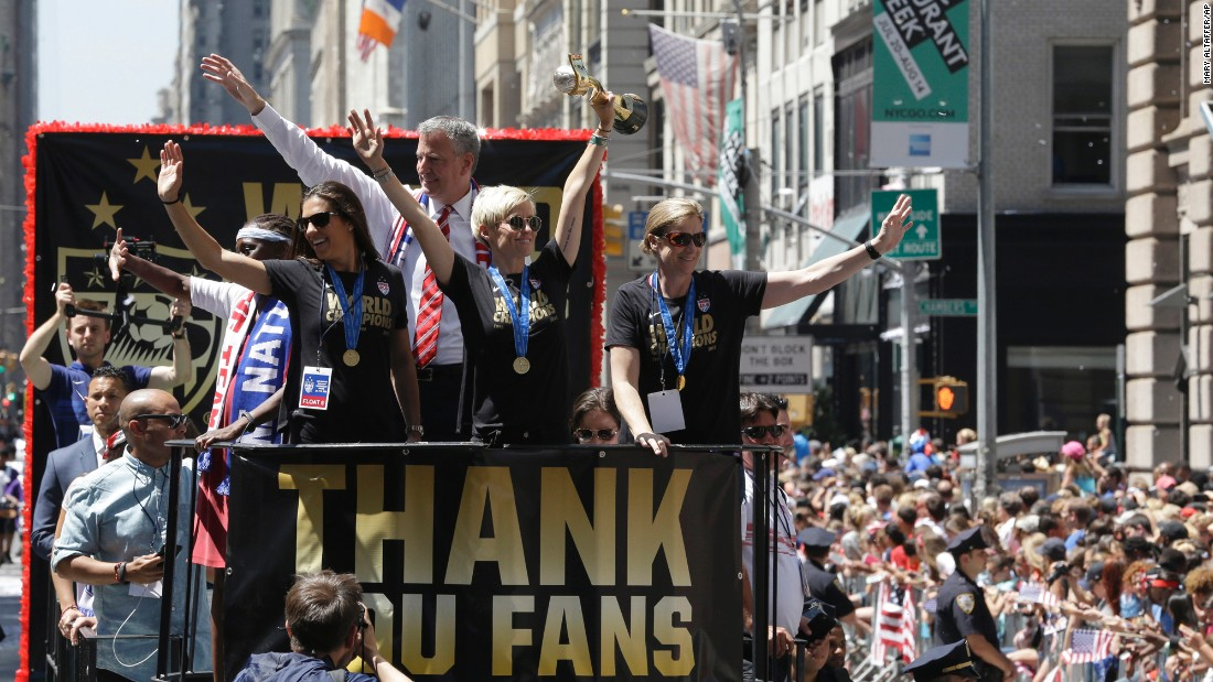 "U.S. soccer player Megan Rapinoe holds up the Women's World Cup trophy as teammate Carli Lloyd, left, and head coach Jill Ellis, right, wave to fans during <a href=""http://www.cnn.com/2015/07/10/us/gallery/us-soccer-team-parade/index.html"" target=""_blank"">a parade in New York City</a> on Friday, July 10. Behind Rapinoe is New York Mayor Bill de Blasio."