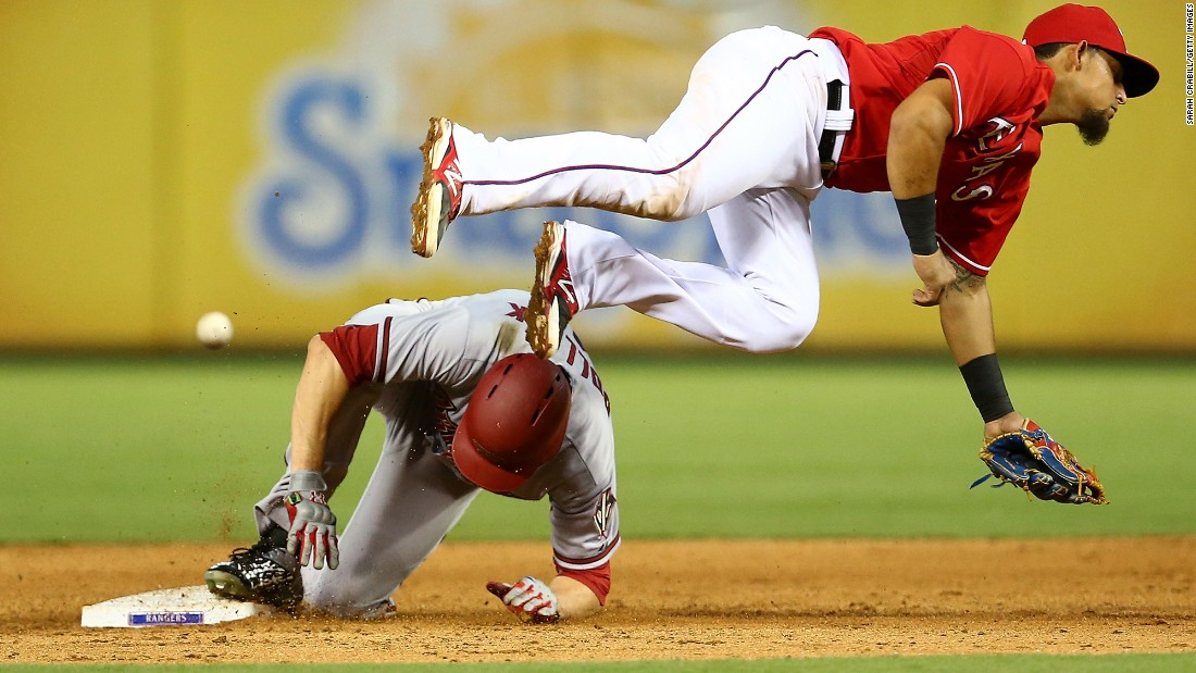 Arizona's A.J. Pollock slides safely into second base as the ball flies past Texas' Rougned Odor on Tuesday, July 7.