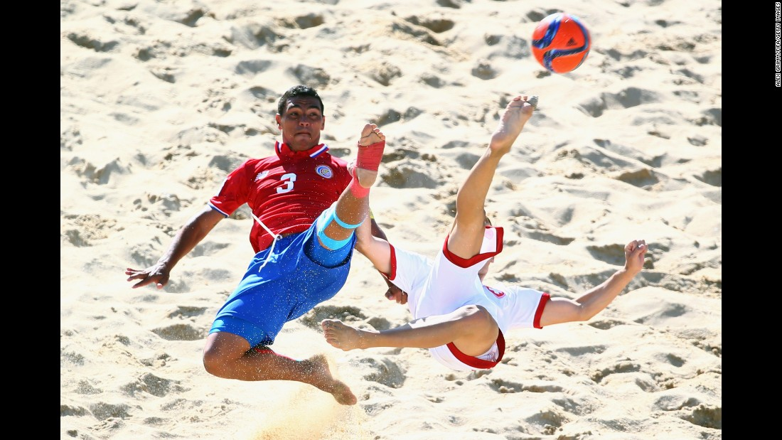 Costa Rica's Jose Mendoza, left, and Switzerland's Noel Ott reach for a ball during a match at the Beach Soccer World Cup on Saturday, July 11. Switzerland won the match 4-3 in Espinho, Portugal.