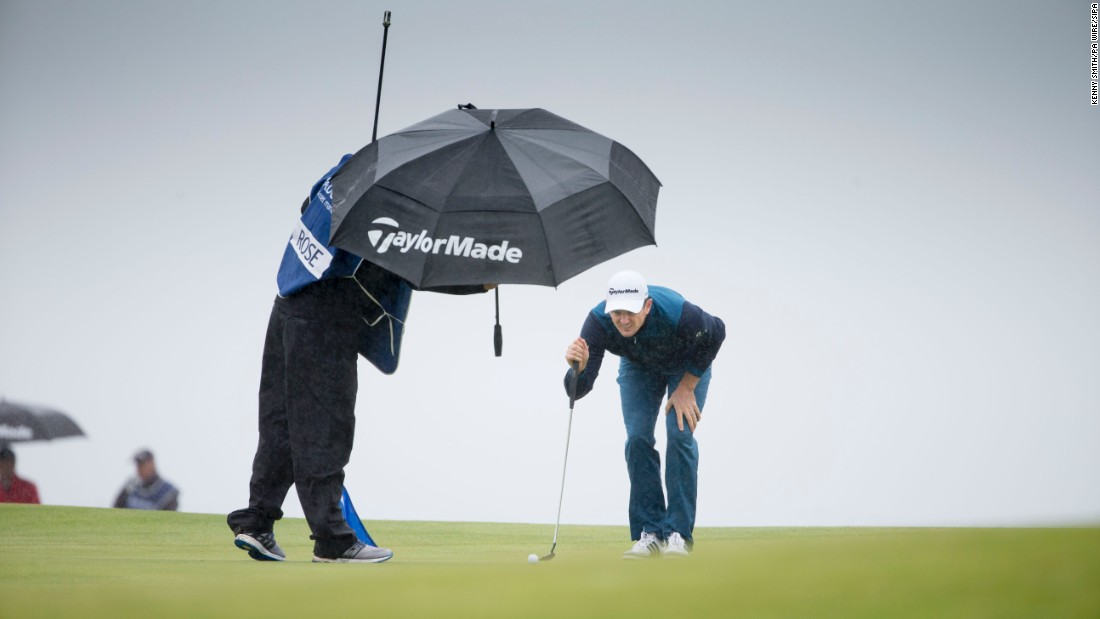 Justin Rose tries to keep dry as he lines up a putt at the Scottish Open on Friday, July 10.