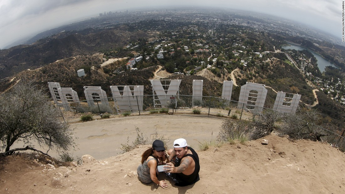 Two people take a selfie behind the famous Hollywood sign in Los Angeles on Thursday, July 9.