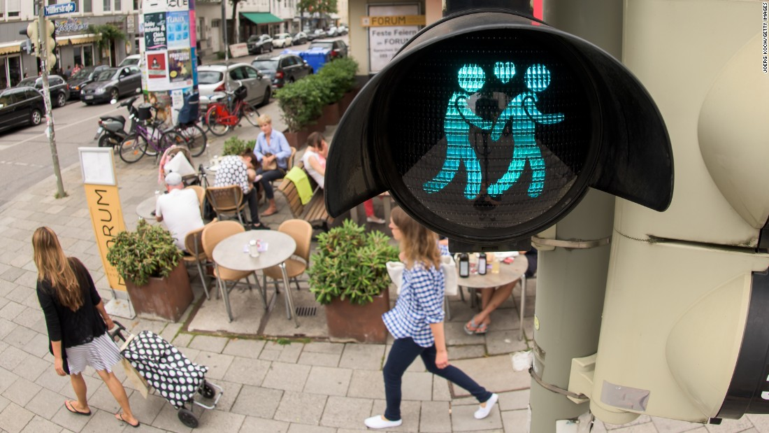 A pedestrian crossing signal shows a same-sex male couple at a junction in Munich on July 14. The figures glow in red and green at pedestrian crosswalks, showing both female and male couples.