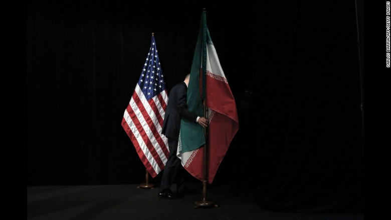A staff removes the Iranian flag from the stage after a group picture with foreign ministers and representatives of Unites States, Iran, China, Russia, Britain, Germany, France and the European Union during the Iran nuclear talks at Austria International Centre in Vienna, Austria on July 14, 2015. Major powers clinched a historic deal aimed at ensuring Iran does not obtain the nuclear bomb, opening up Tehran's stricken economy and potentially ending decades of bad blood with the West.