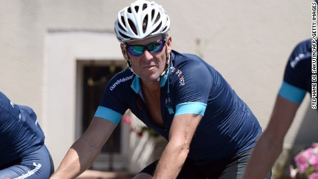 US cyclist Lance Armstrong (C) arrives for lunch during the two stages of cycling of The Tour De France for a leukaemia charity a day ahead of the competing riders, on July 16, 2015 , in Villefranche d'Albigeois, southwest France. For the first time since he was stripped of his seven Tour de France titles, disgraced cyclist Lance Armstrong rode a stage of the famous race for charity. Armstrong, 43, was riding a 198-kilometre (123-mile) stage a day ahead of the competing riders for a leukaemia charity but cycling officials have branded the exercise 'disrespectful'. AFP PHOTO / STEPHANE DE SAKUTIN (Photo credit should read STEPHANE DE SAKUTIN/AFP/Getty Images)
