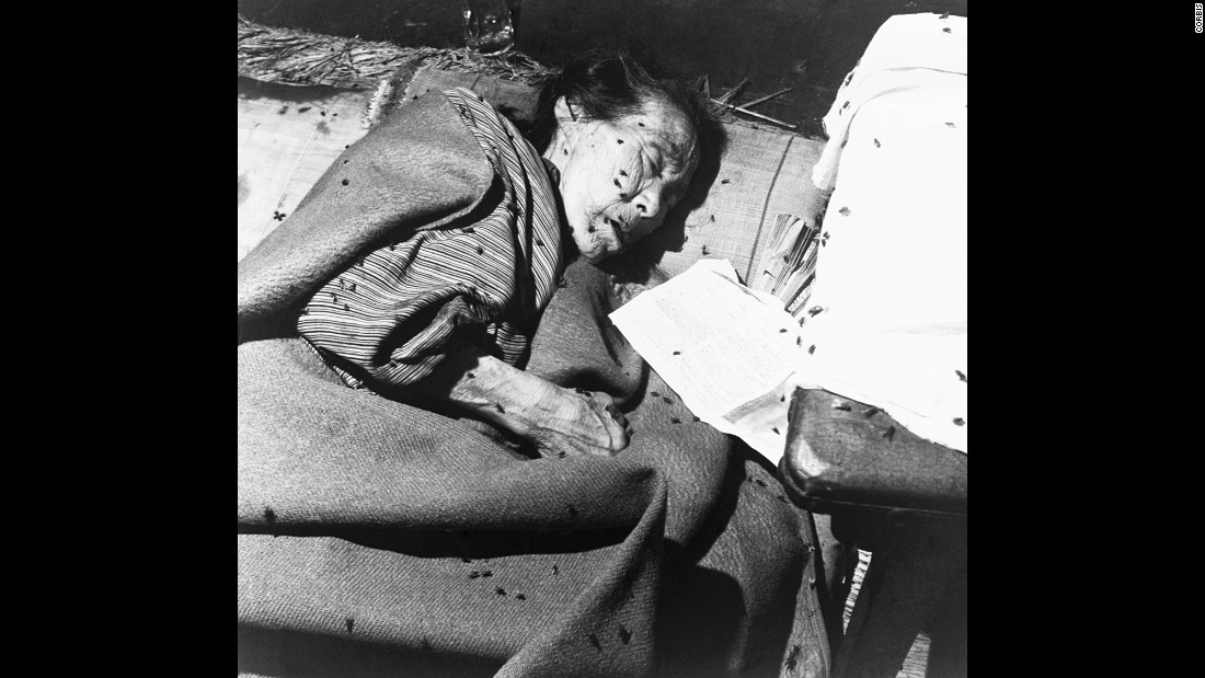 An elderly victim is covered with flies in a makeshift hospital in Hiroshima.