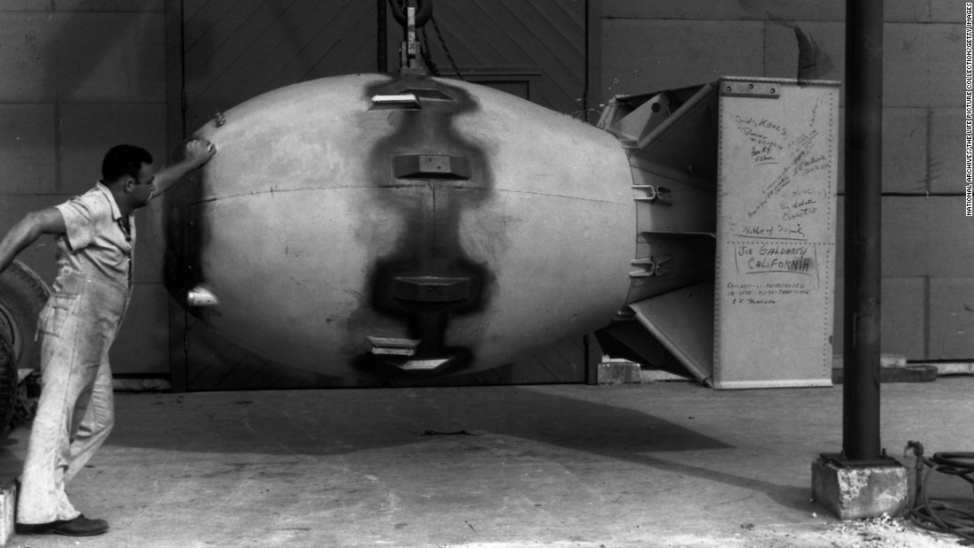 "A worker stands next to an atomic bomb, nicknamed ""Fat Man,&quot"