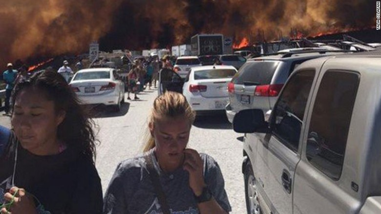 People flee their vehicles after being stopped on I-15 near San Bernardino, California, by a wildfire that jumped onto the highway, torched numerous vehicles and caused injuries.