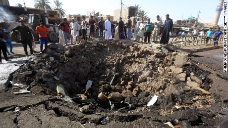 Men stand near the crater left by a massive suicide car bomb attack carried out by ISIS in the predominantly Shiite town of Khan Bani Saad near Baghdad, Iraq on July 18.