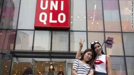 Women take a selfie outside the Uniqlo flagship store in Beijing.
