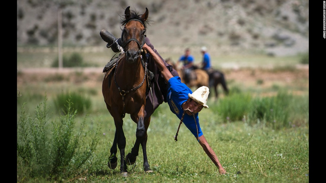 "A man in Kyzyl-Oi, Kyrgyzstan, takes part in the game of ""tyin enmei,"" which involves picking up coins from the ground while racing on horseback, on Saturday, July 18. Horses have always played a huge role in the daily life of the Kyrgyz people. The majority of the rural population follows a semi-nomadic way of life. Almost everyone can ride a horse, and horse games have been passed from generation to generation."